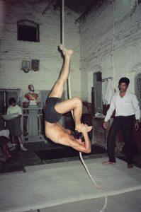 Simon Borg-Olivier practicing eka pada viparita dandasaana on rope Mallakhamb in Pune, India, 1988